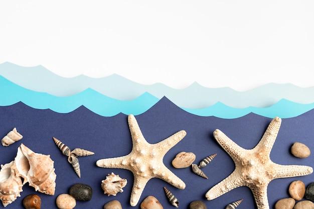 Vista superior das ondas do mar de papel com estrelas do mar e conchas do mar