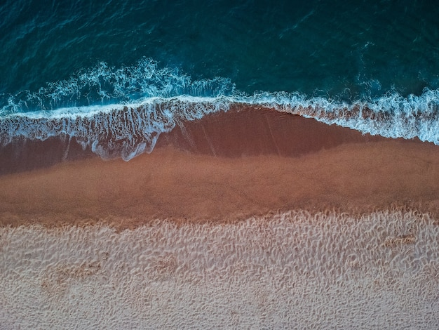 Vista superior das ondas na praia arenosa da ilha de creta