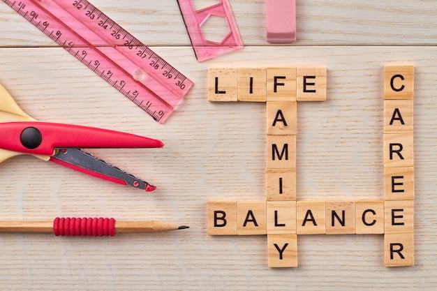 Vista superior das palavras cruzadas com o conceito de equilíbrio de carreira. artigos de papelaria e blocos de madeira com letras na placa de madeira.
