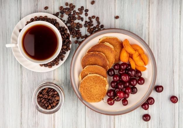 Vista superior das panquecas com cerejas e fatias de damasco no prato e xícara de chá com grãos de café no pires e na jarra com fundo de madeira