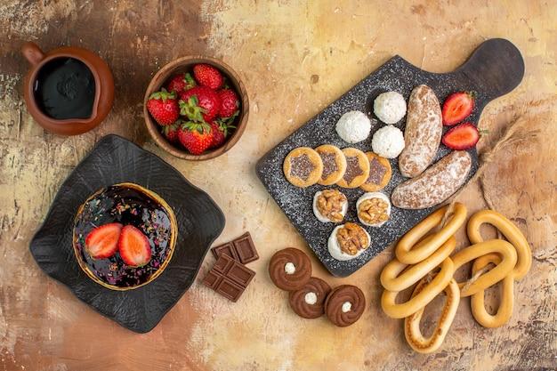 Vista superior das panquecas doces com frutas e doces na mesa de madeira