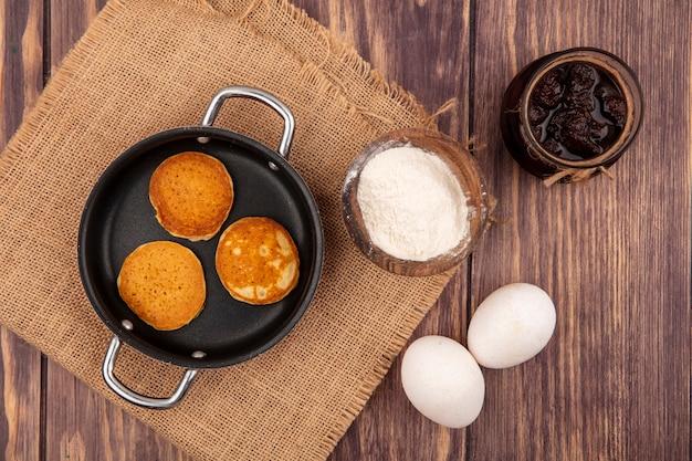 Vista superior das panquecas na panela e farinha em uma tigela de saco com ovos e geleia de morango no fundo de madeira