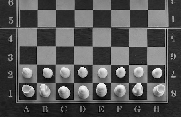 Vista superior das peças brancas no tabuleiro de xadrez em preto e branco conceito de estratégia de jogo de xadrez