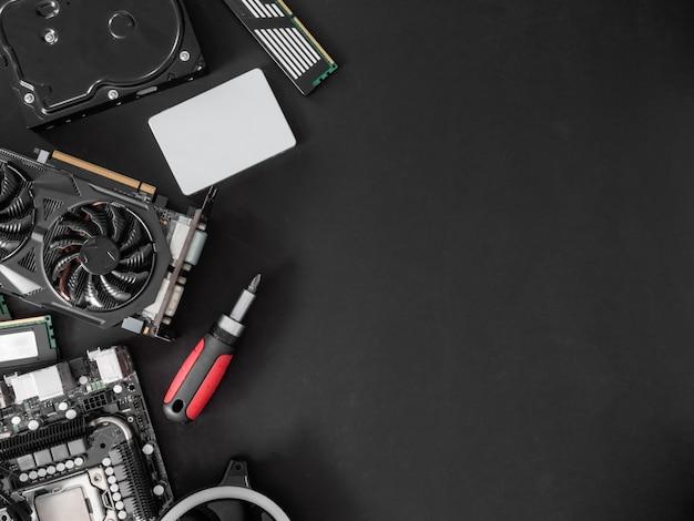 Vista superior das peças do computador com disco rígido, memória ram, cpu, placa gráfica e placa-mãe no fundo preto da tabela.
