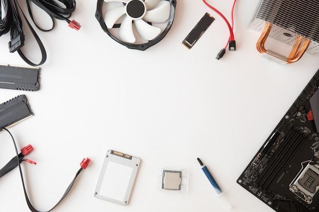 Vista superior das peças e acessórios do computador, reparo da eletrônica e atualização no fundo branco da mesa, espaço da cópia. placa-mãe, processador cpu, cooler, radiador, configuração plana.
