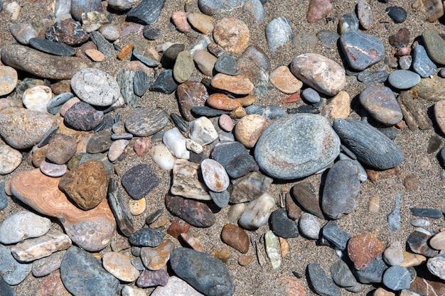 Vista superior das pedras da praia e conceito de textura de fundo de areia