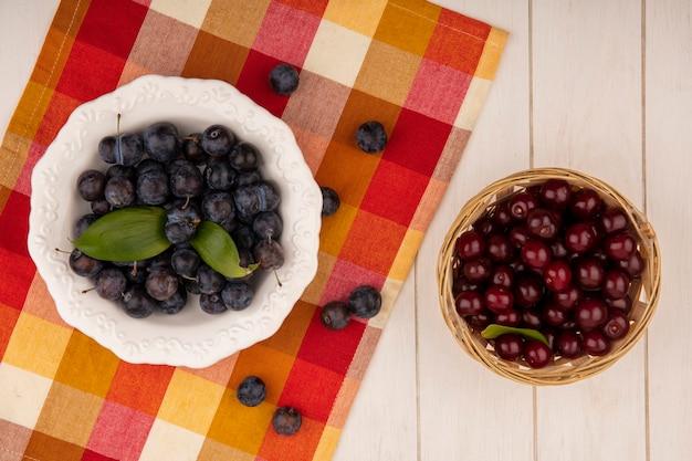 Vista superior das pequenas abrunhas de frutas azedas azuladas em uma tigela branca sobre uma toalha de mesa quadriculada com cerejas vermelhas em um balde sobre um fundo branco