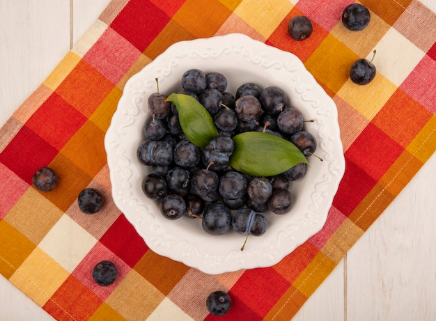 Vista superior das pequenas abrunhas de frutas azedas azuladas em uma tigela branca sobre uma toalha de mesa quadriculada em um fundo branco