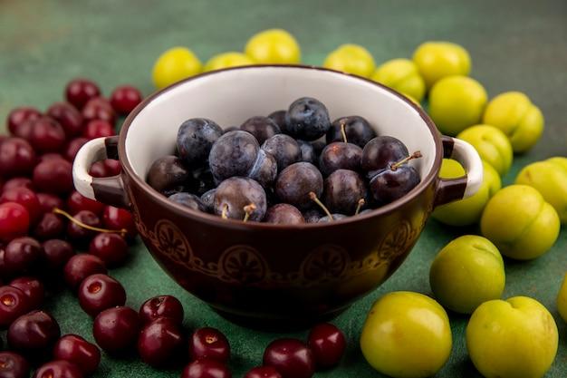 Vista superior das pequenas abrunhas de frutas azedas azuladas em uma tigela marrom com cerejas vermelhas e ameixas verdes em um fundo vermelho