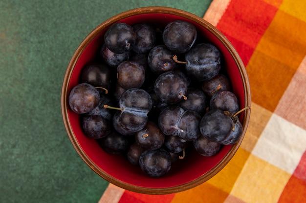 Vista superior das pequenas abrunhas de frutas azedas em uma tigela vermelha sobre uma toalha de mesa quadriculada em um fundo verde