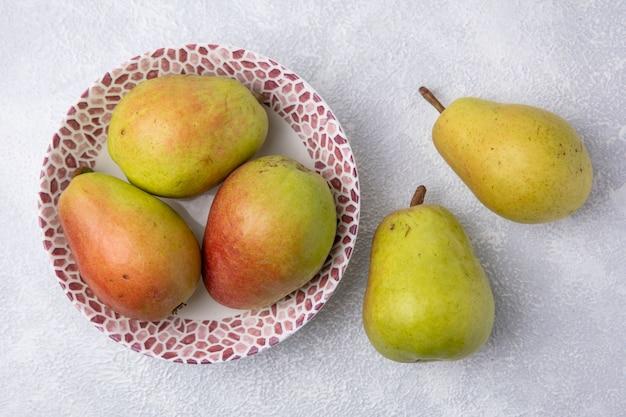 Vista superior das peras em um prato em um fundo branco