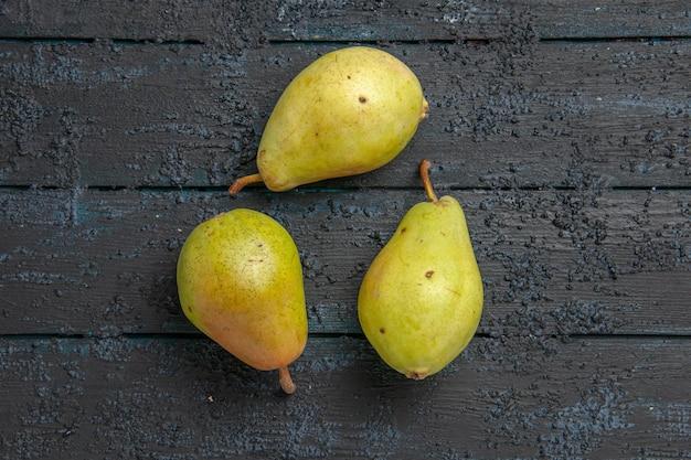 Vista superior das peras na mesa três peras verdes dispostas em um círculo na mesa cinza