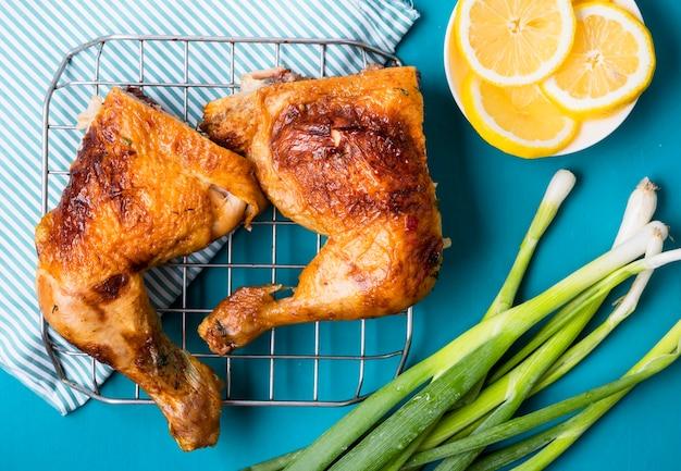 Vista superior das pernas de frango com rodelas de limão e cebolinha