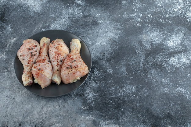 Vista superior das pernas de frango marinado cru na placa preta.