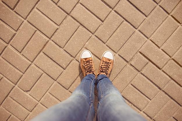 Vista superior das pernas de uma garota em sapatos desportivos e jeans na calçada