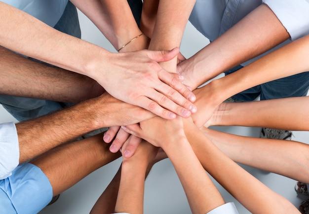 Vista superior das pessoas em círculo com as mãos juntas
