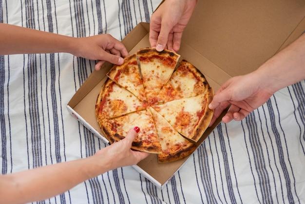 Vista superior das pessoas pegando uma fatia de pizza
