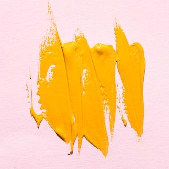 Vista superior das pinceladas de tinta amarela na superfície