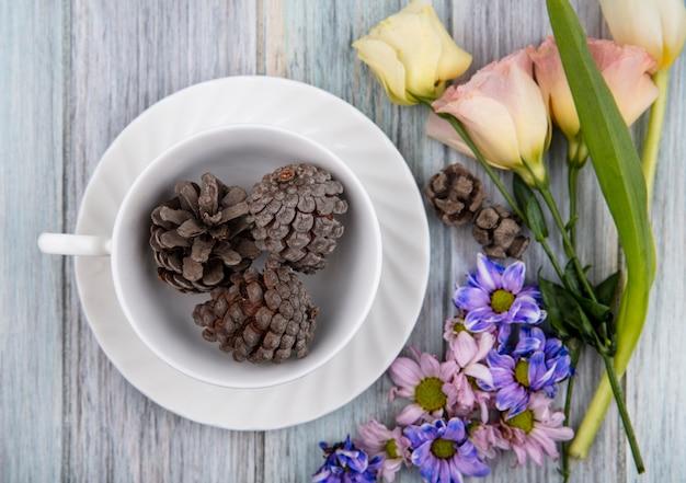 Vista superior das pinhas na xícara no pires e flores no fundo de madeira