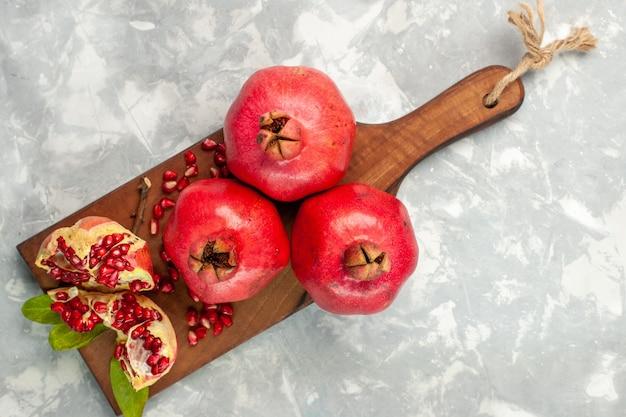 Vista superior das romãs vermelhas frescas e frutas ácidas e maduras na mesa branca
