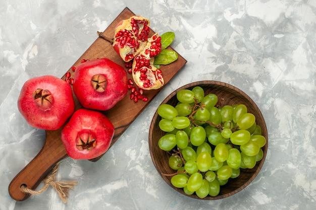 Vista superior das romãs vermelhas frescas, frutas ácidas e maduras com uvas verdes em uma mesa branca