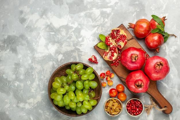 Vista superior das romãs vermelhas frescas, frutas azedas e maduras com uvas verdes frescas na mesa branca