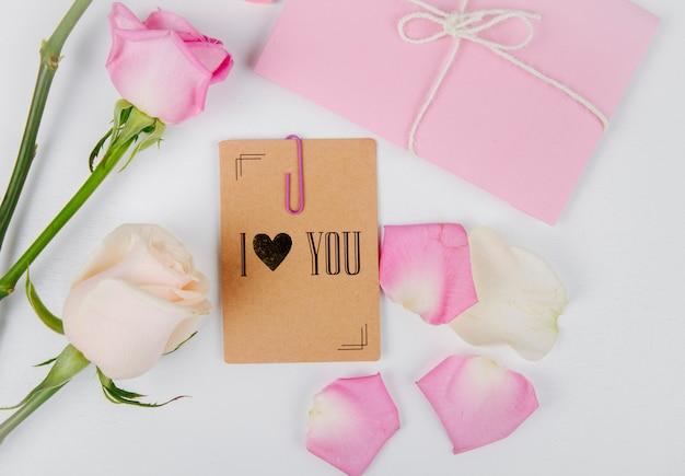 Vista superior das rosas de cor branca e rosa com envelope amarrado com uma corda e pequeno cartão postal com um clipe de papel e pétalas de flores rosa em fundo branco