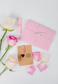 Vista superior das rosas de cor branca e rosa com envelope amarrado com uma corda e pequeno cartão postal com um clipe de papel no fundo branco