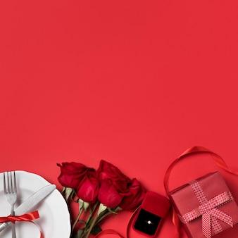 Vista superior das rosas do dia dos namorados com presente e anel de noivado