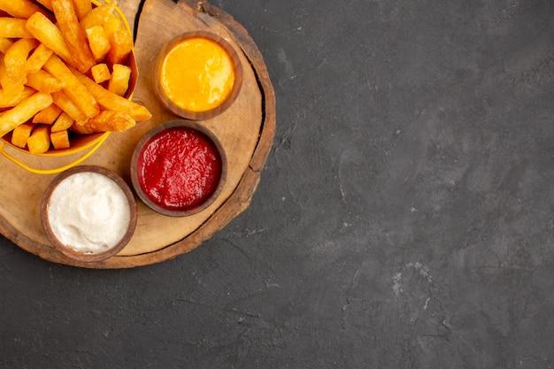 Vista superior das saborosas batatas fritas com molhos na mesa preta