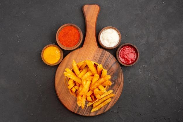 Vista superior das saborosas batatas fritas com molhos no preto