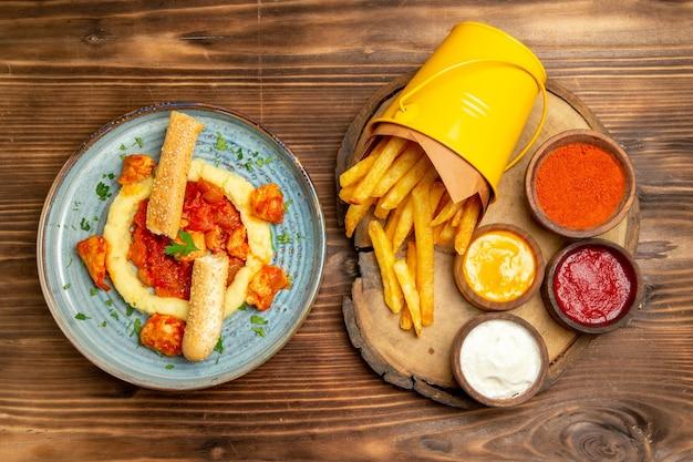 Vista superior das saborosas batatas fritas com temperos e farinha de frango na mesa marrom
