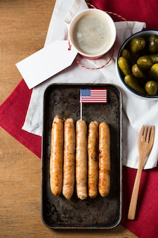 Vista superior das salsichas fritas na bandeja com a bandeira americana