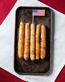 Vista superior das salsichas na bandeja com a bandeira americana