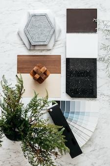 Vista superior das seleções de materiais, incluindo ladrilho de granito, ladrilho de mármore, ladrilho acústico, laminado de madeira de nogueira e cinza e amostra de cor pintada com plantas e flores na mesa superior de mármore.