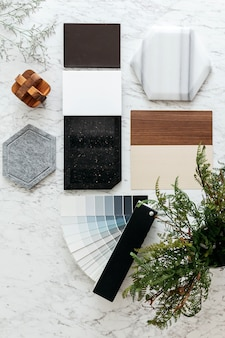 Vista superior das seleções de materiais, incluindo telha de granito, telha de mármore, telha acústica, noz e ash wood laminado e álbum de tons de cores pintadas com plantas e flores na mesa superior de mármore.