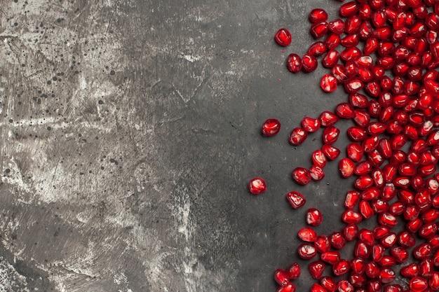 Vista superior das sementes de romã na superfície escura