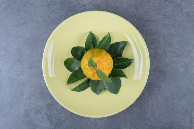 Vista superior das tangerinas frescas com folhas na placa amarela.
