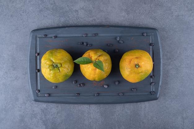 Vista superior das tangerinas frescas na placa de madeira cinza.