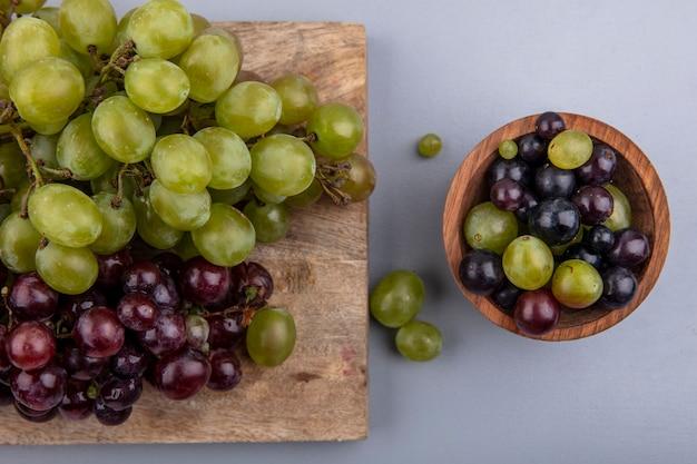 Vista superior das uvas brancas e vermelhas na tábua e na tigela de bagas de uva no fundo cinza