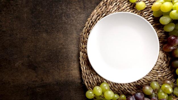 Vista superior das uvas de outono com prato e espaço de cópia