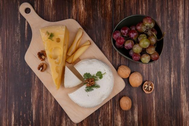 Vista superior das uvas em uma tigela com maasdam, queijo feta e nozes em um suporte sobre um fundo de madeira