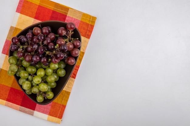 Vista superior das uvas em uma tigela sobre um pano xadrez em fundo branco com espaço de cópia