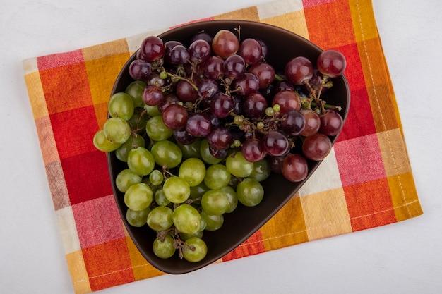 Vista superior das uvas em uma tigela sobre um pano xadrez em fundo branco