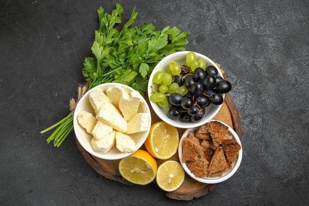 Vista superior das uvas frescas com queijo branco e rodelas de limão na superfície escura.