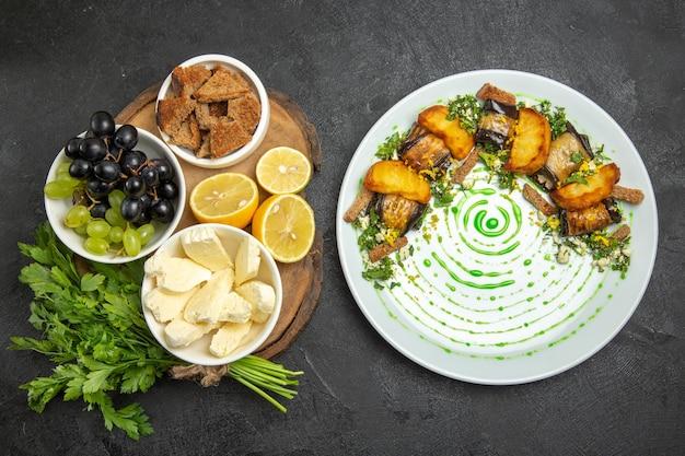 Vista superior das uvas frescas com queijo branco, verdes e limão na superfície escura, refeição com leite, frutas