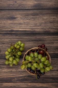 Vista superior das uvas na cesta e no fundo de madeira com espaço de cópia