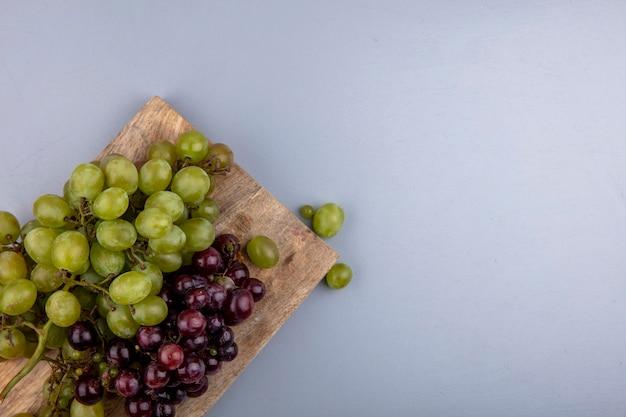 Vista superior das uvas na tábua em fundo cinza com espaço de cópia