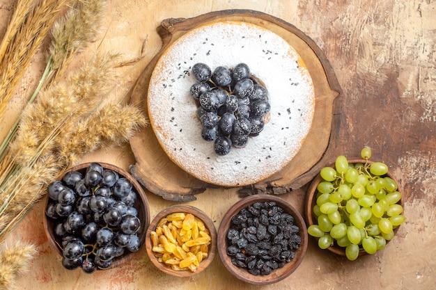Vista superior das uvas, um bolo com uvas no tabuleiro taças de espigas de uvas passas