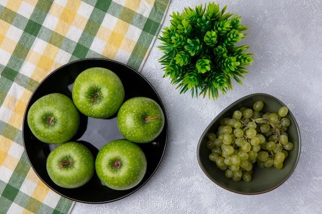 Vista superior das uvas verdes em uma tigela de maçãs verdes com uma toalha xadrez verde-amarelo em um fundo branco